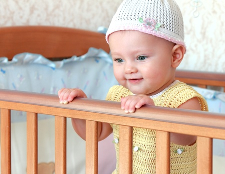 Beautiful happy baby girl in funny white hat standing in bed photo