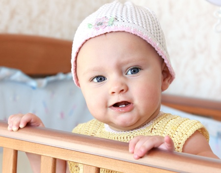 Beautiful angry baby girl in funny hat standing in bed with opened mouth and looking photo