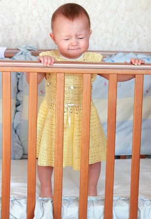 angry baby: Pretty small crying baby girl  standing in wooden bed in yellow dress