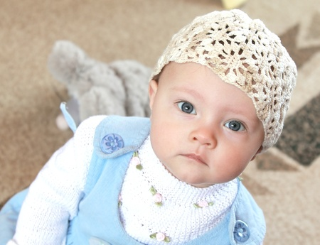 Serious baby in funny hat and blue dress sitting and looking in camera photo
