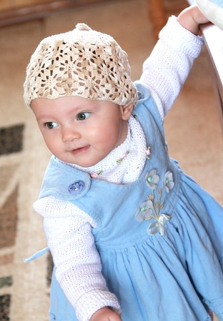 Portrait of standing baby girl in blue dress and white summer hat and looking Stock Photo - 12776498