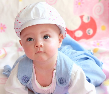 Beautiful happy thinking looking up with interest baby girl in funny hat lying  in blue dress photo