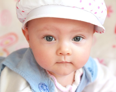 Closeup portrait of serious thinking baby girl in funny hat photo