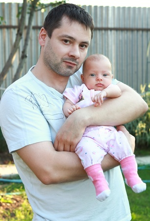 Portrait of handsome father holding little baby girl on the hands with love on nature background photo