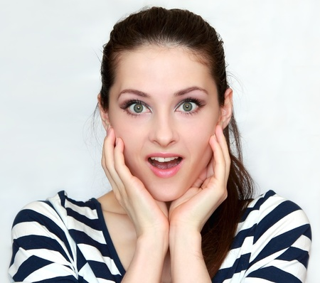 Beautiful young happy woman holding hands to face in surprise. Closeup portrait Stock Photo - 13000460