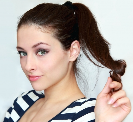 flirting women: Beautiful young woman holding the long hair with flirting look. Closeup portrait of 20s green eyes girl
