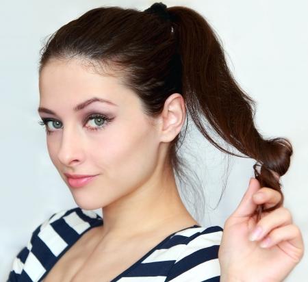 coquetear: Joven y bella mujer sosteniendo el pelo largo con coquetear mirada. Retrato de la ni�a de ojos verdes 20 a�os