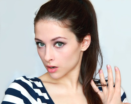 Closeup portrait of a surprised young woman holding hand the hair and looking with big eyes and opened mouth isolated Stock Photo - 13000507