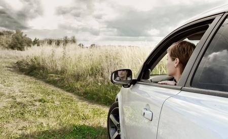 Piękna kobieta, patrząc z okna samochodu sportowego o charakterze ciemnego nieba i zielonym tle trawy letni dzień młodej damy siedzącej i jazdy auto