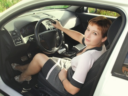 New sport car  Portrait of beautiful woman sitting inside the sport auto and looking out with smiling   photo