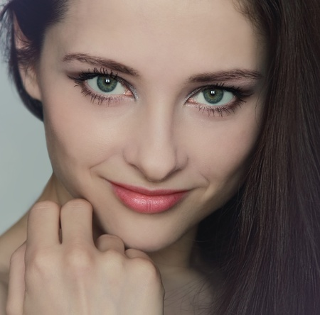 Closeup portrait of sexy young beautiful woman with hand near the face with green eyes and red lips Stock Photo - 13309639