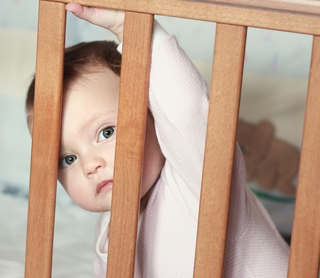 Adorable funny baby boy looking out the wooden bed with big eyes photo
