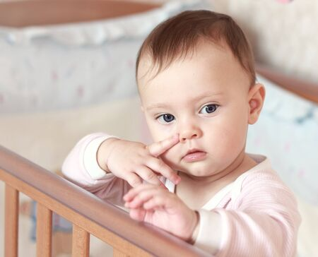 Funny small baby girl holding finger near the nose on face standing in bed and looking at Stock Photo - 13333883