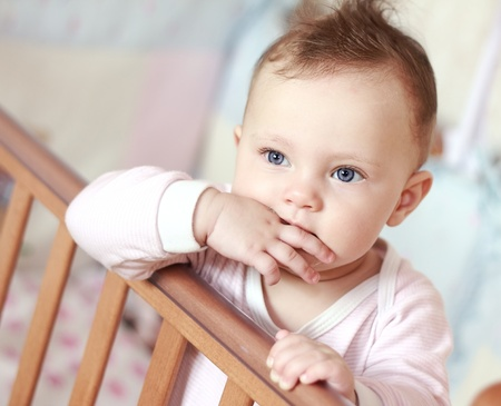 Funny small baby sucking fingers standing in bed and looking  Closeup portrait Stock Photo - 13375782