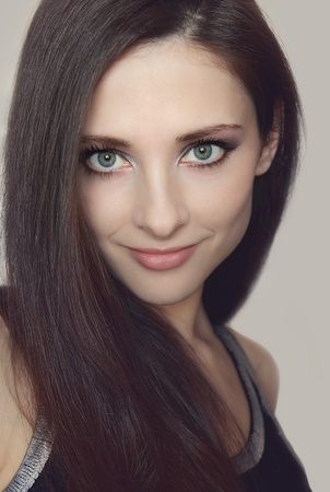 Young woman with healthy long hair and green eyes looking  Closeup soft portrait photo