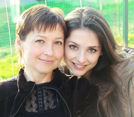Portrait of happy beautiful mother and adult smiling daughter on nature bright green background looking Stock Photo - 13422562