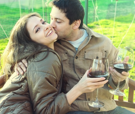 Happy couple drinking red wine outdoor  Young man kissing laughing beautiful girl with long hair  She is looking in camera  Closeup bright portrait of happiness and leisure with drink in sunny summer day photo