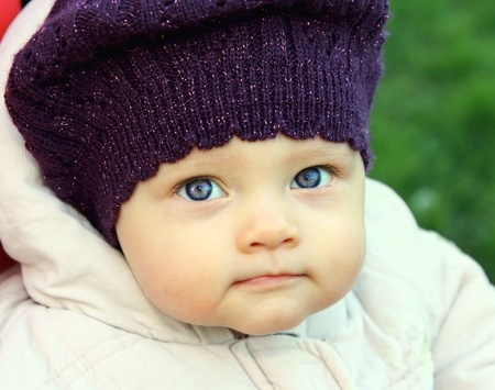 Beautiful funny baby in hat with big blue eyes looking on nature green background  Closeup portrait photo