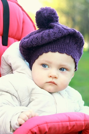 Funny baby girl in hat outdoor sitting in stroller and looking  Closeup portrait photo