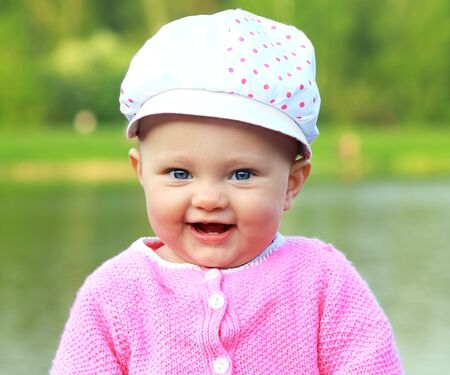 Beautiful smiling pink cheeks baby girl in pink dress and hat on nature green background photo