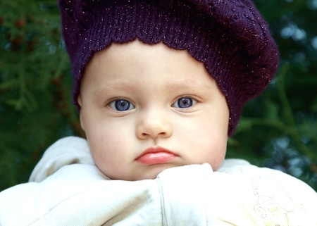 Funny baby in hat outdoors with chubby bright lips and cheeks looking serious on green trees background Stock Photo - 13566038