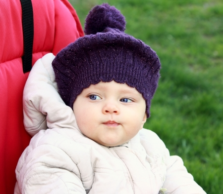 Funny baby in hat outdoot sitting in red bright stroller on green grass background photo
