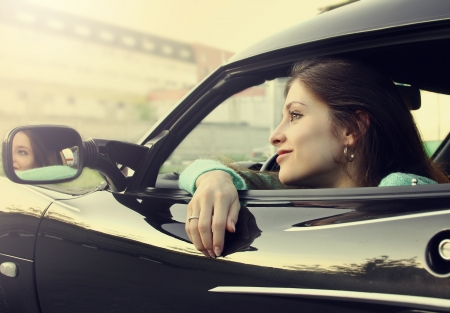 Beautiful smiling girl sitting in new sport car and looking from window  Stock Photo