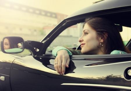 Piękna uśmiechnięta dziewczyna siedzi w nowym samochodzie sportowym i patrząc z okna