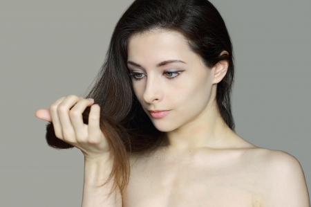 Woman holding long hair with damaged ends and looking unhappy  Closeup isolated portrait   Hair care concept photo