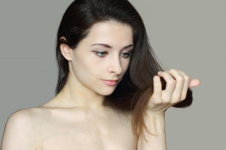 Woman holding damaged hair and unhappy looking  Closeup isolated portrait of beautiful upset lady  Hair care concept Stock Photo - 14031854