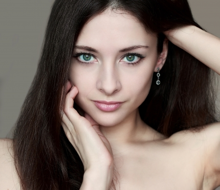 Fashion portrait of woman with sexy look holding face and long hair isolated Stock Photo - 14123097