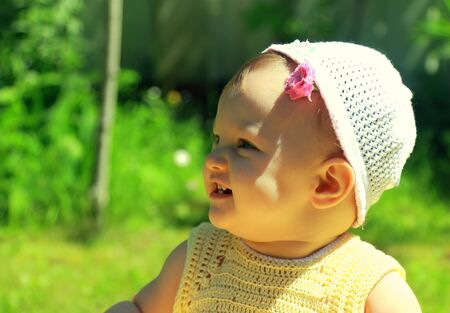 Closeup portrait of fun smiling baby girl in hat on green grass background Stock Photo - 14122963