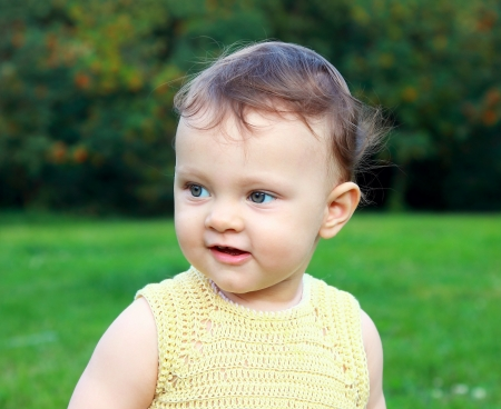 Portrait of beautiful baby girl smiling and looking on summer nature  Green grass and green trees outdoors Stock Photo - 14615740