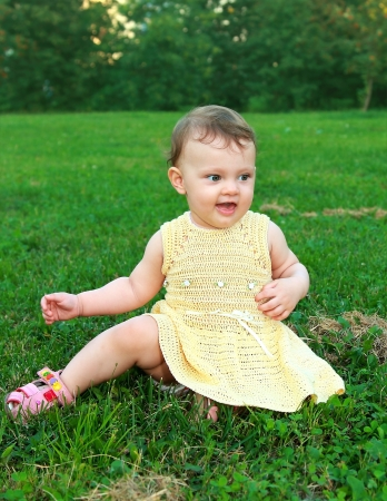 Beautiful happy baby girl sitting on green grass on nature background Stock Photo - 14615852