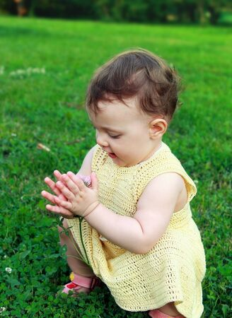 Beautiful baby girl holding flower and looking sitting on green grass photo