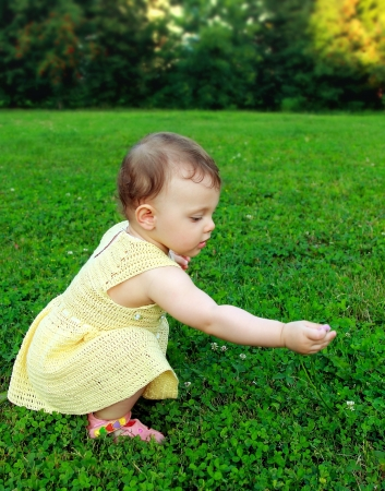 Beautiful baby girl picking flowers and looking sitting on nature green grass photo