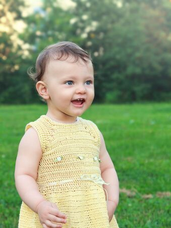 Happy baby girl looking with open mouth on nature summer green background.  photo