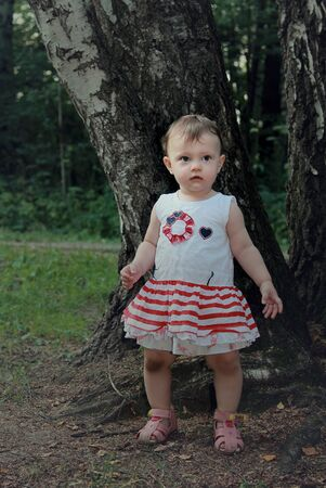 Beautiful lost baby girl in forest near the trees looking with worried eyes photo