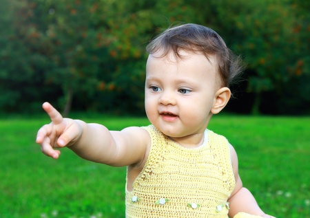 Sweet adorable baby girl showing finger on samething with smiling look on summer green nature background Stock Photo - 14715971