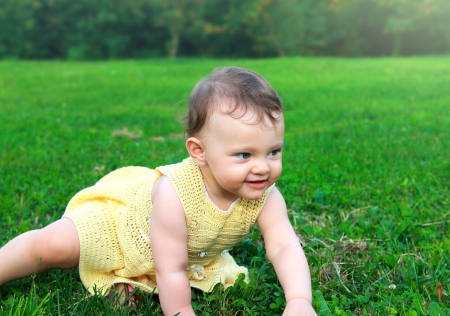 Fun baby girl creeping on green summer green glass with happy smiling Stock Photo - 14715972