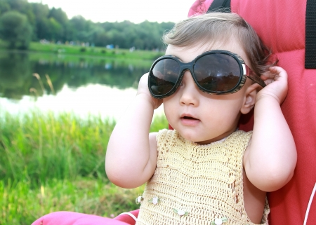 Baby girl in big fun sunglasses outdoors on summer green grass background  Closeup funny portrait Stock Photo - 14715974