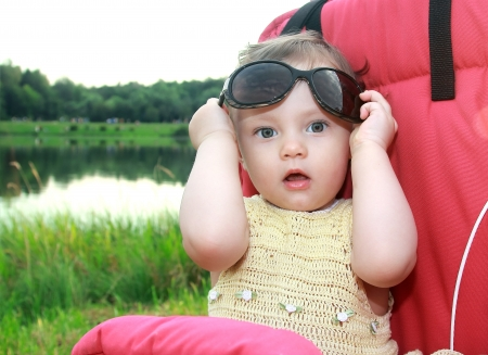 Beautiful surprised baby girl holding sunglasses with opened mouth on nature green background Stock Photo - 14715975