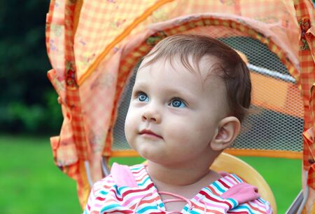 Happy baby face portrait sitting in stroller with nice look outdoor on green summer background  Stock Photo - 14750120