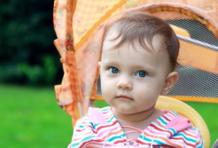 Closeup portrait of baby girl with beautiful blue eyes looking calm sitting in stroller on summer background outdoor Stock Photo - 14750121