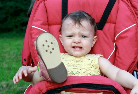 Crying baby girl sitting in stroller outdoor with holding up the leg on nature background  Closeup portrait Stock Photo - 14827390