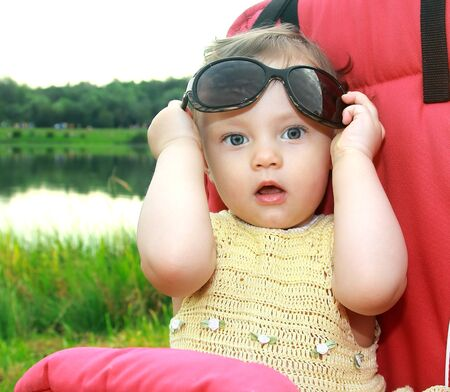 Beautiful surprised baby girl holding sunglasses with opened mouth on nature green background Stock Photo - 14925201