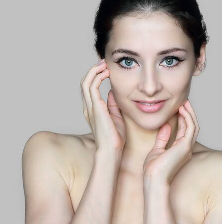 Beauty face of young beautiful woman touching hands the healthy skin with happy smile isolated  Closeup portrait with empty space Stock Photo - 14960928