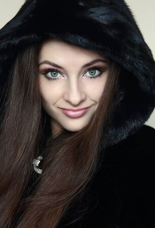 Beautiful smiling woman in fur black hood looking sexy  Closeup portrait photo