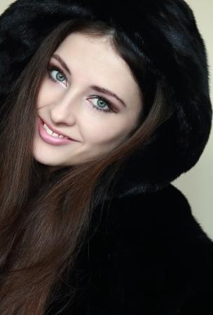 fur hood: Beautiful smiling woman in fur hood coat looking happy  Closeup portrait Stock Photo