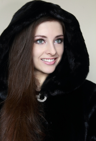 Portrait of beautiful smiling girl in fur hood coat looking happy  Closeup photo